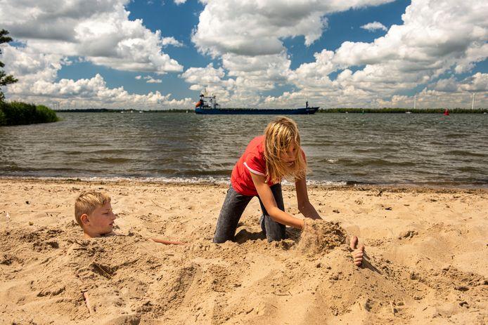Marilène Polak graaft buurjongen Sylvester Koorevaar in op het strandje in De Appelzak, gelegen tussen het dorp Moerdijk en het industriegebied.