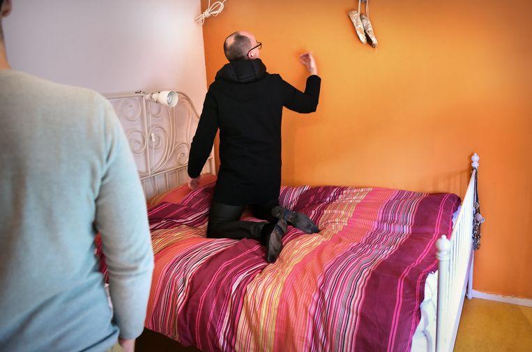 Aankoopmakelaar bekijkt samen met een cliënt een huis en klopt op de muren. Beeld Marcel van den Bergh