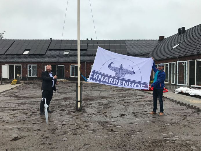 Wethouder Martijn Breukelman hijst de Knarrenhofvlag met eerste bewoner Jan van der Kamp (rechts). Rondom de vlaggenmast worden binnenkort graszoden gelegd.