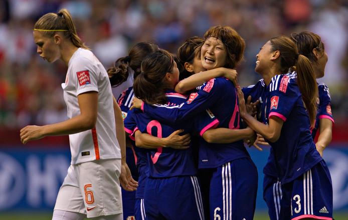 WK 2015: de Japanse middenvelder Mizuho Sakaguchi  wordt gefeliciteerd door haar teamgenoten na het maken van een doelpunt. Anouk Dekker loopt gefrustreerd weg.