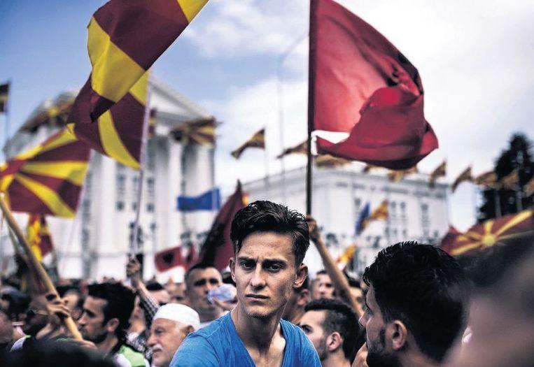 Demonstranten zwaaien in Skopje met Albanese (rechts) en Macedonische vlaggen terwijl ze het aftreden van de regering van premier Gruevski eisen. Beeld afp
