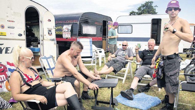 Bezoekers van het festival Zwarte Cross in Lichtenvoorde drinken een biertje voor de caravan. Beeld Herman Engbers