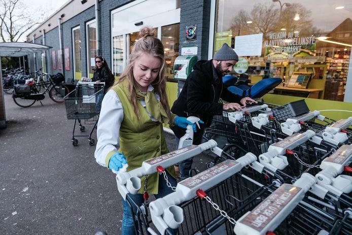 Een medewerkster van de Plus in Winterswijk reinigt de winkelkarretjes. Foto ter illustratie.