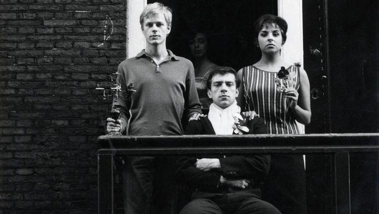 Ramses Shaffy voor zijn huis in de Derde Weteringdwarsstraat, met links zijn toenmalige liefde Joop Admiraal en rechts vriendin Shireen Strooker, tijdens de opnamen voor 'Zij drieën' van de Vara (3 oktober 1960). Beeld Hollandse Hoogte