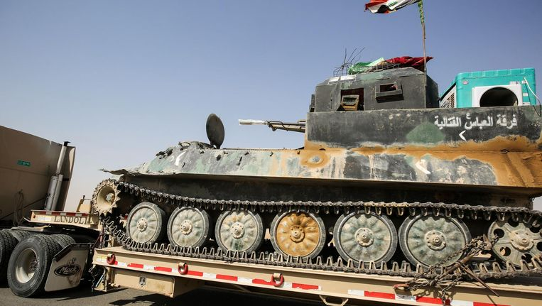 Een gemodificeerd pantservoertuig gebruikt door geallieerde rebellen wordt weggesleept door het Iraakse leger na de overwinning. Beeld afp