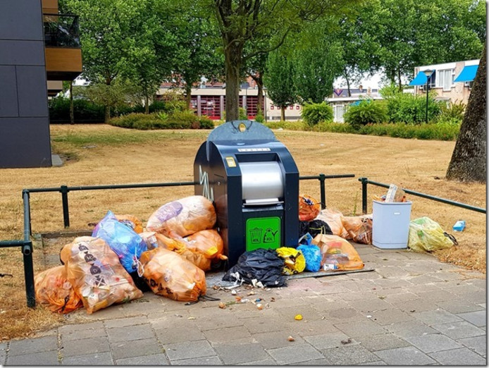 Rond de ondergrondse afvalcontainer hoopt het vuilnis zich op.