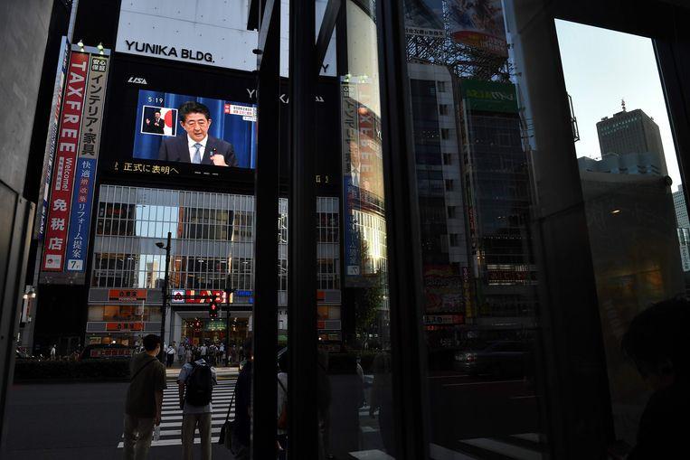 Japanse premier Shinzo Abe kondigt zijn vertrek aan, via het beeldscherm in Tokio. Beeld AFP