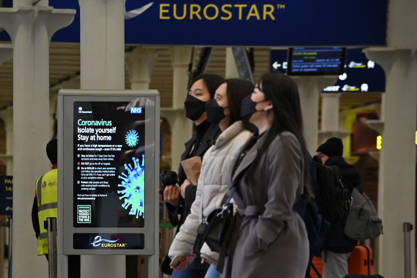 Met gezichtsmaskers op lopen mensen in Eurostar terminal in Londen langs een bord dat hen het advies geeft thuis te blijven. (Foto AFP)