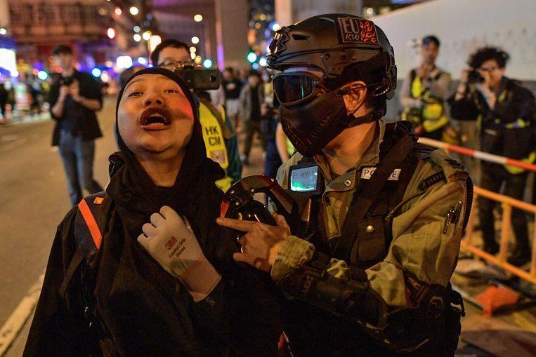 De oproerpolitie voert een demonstrant af om haar identiteit te controleren. Beeld AFP