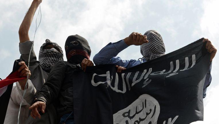 Mannen houden een IS-vlag omhoog. Beeld belga
