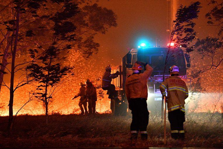 Brandweerlui zijn vrijwilligers uit de gemeenschap zelf. Ze werken al wekenlang voor niets.  Beeld AFP