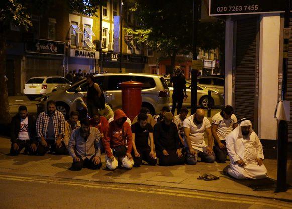 Moslims bidden op de stoep bij de plek waar een bestelwagen eerder in de nacht inreed op een groepje voetgangers dat net de moskee verlaten had.