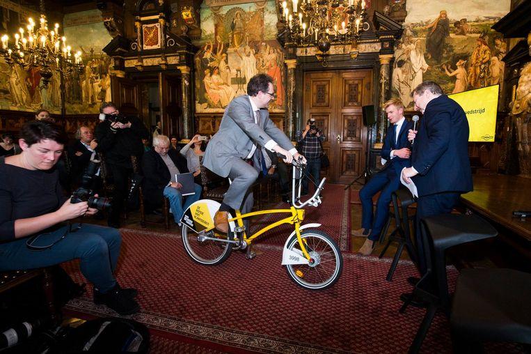 Als je een originele foto neemt op een gele Velo-fiets, die verspreid staan in de stad, dan maak je kans om tijdens de Ronde in een volgwagen te zitten.