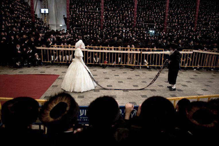 Toeschouwers bij de huwelijksceremonie van een vooraanstaand lid van de chassidisch-joodse gemeenschap in Jeruzalem, afgelopen mei. Beeld EPA