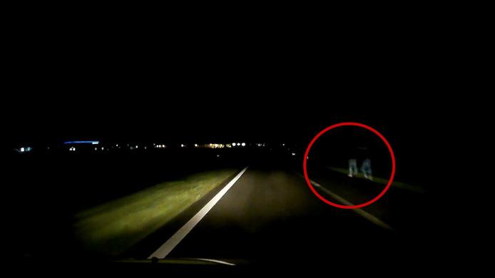 De voetgangers zijn amper te zien langs de donkere weg.