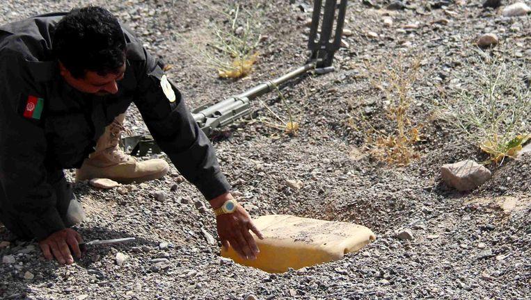 Een Afghaanse politieman verwijdert een landmijn.