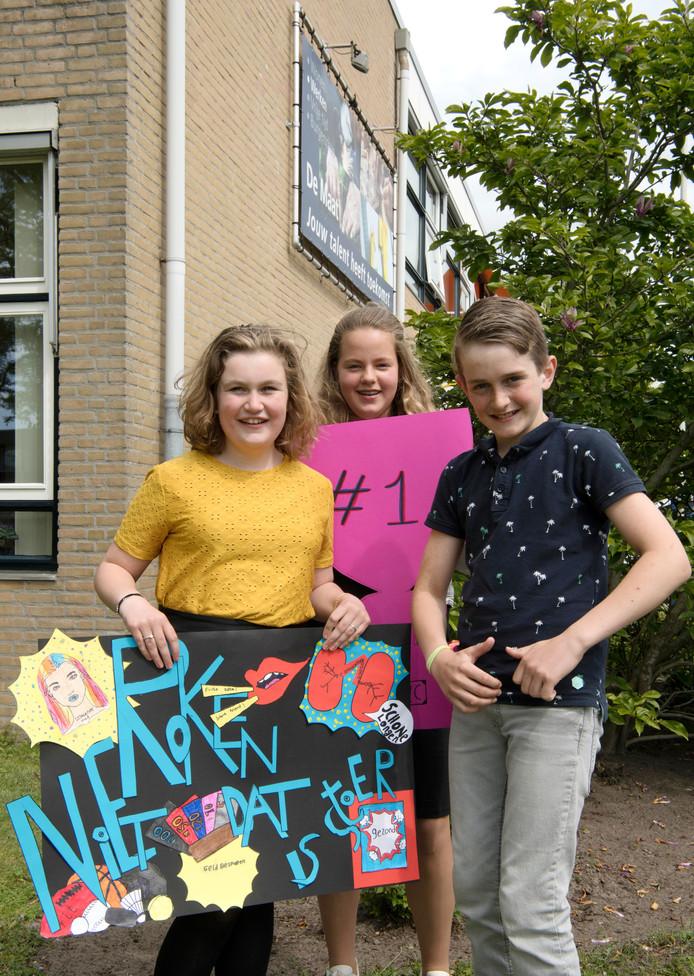 Leerlingen Fleur, Anouk en Time tonen de winnende poster met als slogan 'Niet roken dat is stoer!'.