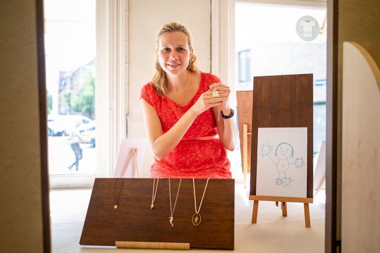 Annemarie Moerman in haar vitrine, met enkele juwelen en een tekening van haar dochter.