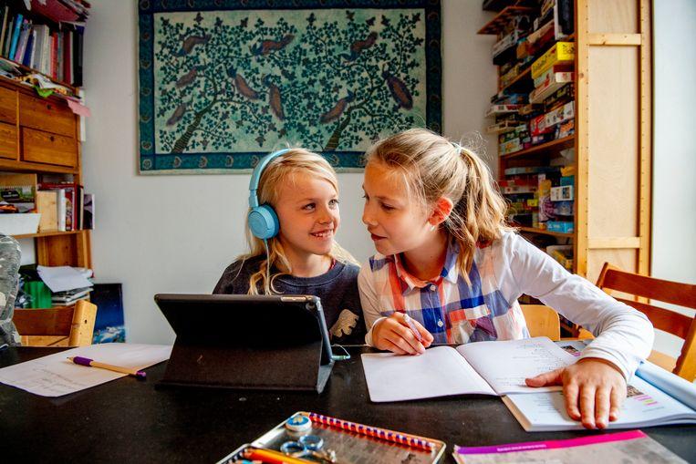 Twee meisjes leren thuis omdat hun school gesloten is. Beeld Robin Utrecht / SOPA