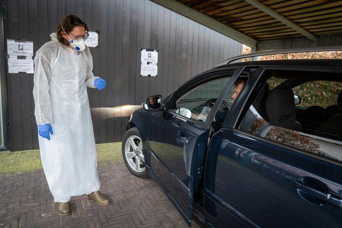 Een huisarts in beschermende kleding wacht een patiënt op die per auto arriveert.