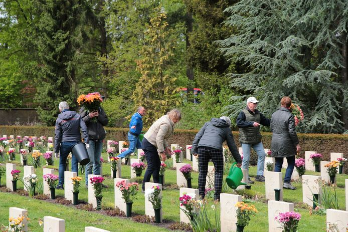 Adoptanten en vrijwilligers plaatsen bloemen op de geadopteerde graven.