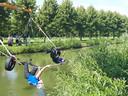 Links Froukje Berkenbosch en Marlies Hermans in apenhang boven het water. Als extra hindernis passeren ze onderlangs twee autobanden.