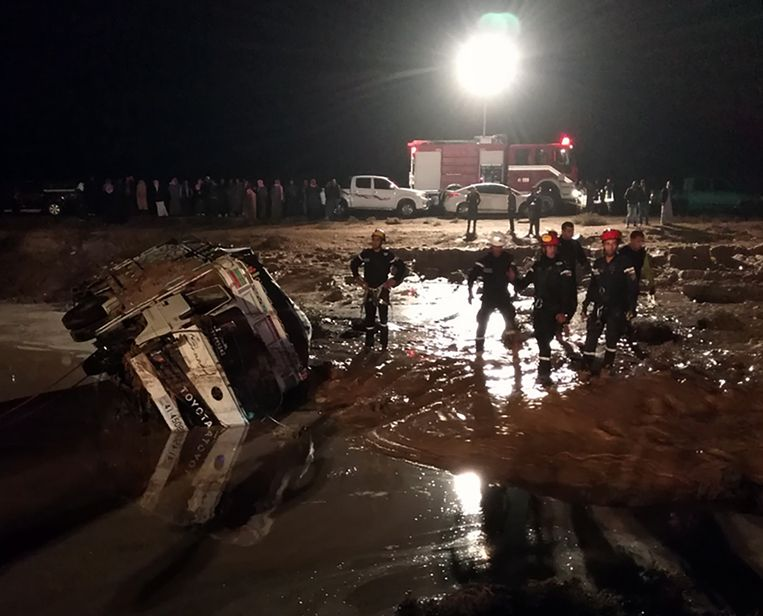 Medewerkers van de Jordaanse civiele bescherming werken aan een weg die beschadigd werd door de plotse overstromingen.