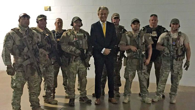 Geert Wilders poseert met leden van de speciale politie-eenheid SWAT voor aanvang van de cartoonwedstrijd. Beeld afp