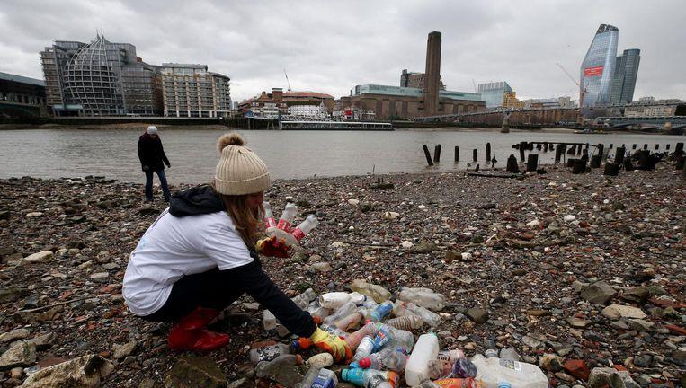 Vrijwilligers verzamelen plastic afval op de oevers van de Theems in hartje Londen. Beeld Hollandse Hoogte / PA Photos Ltd