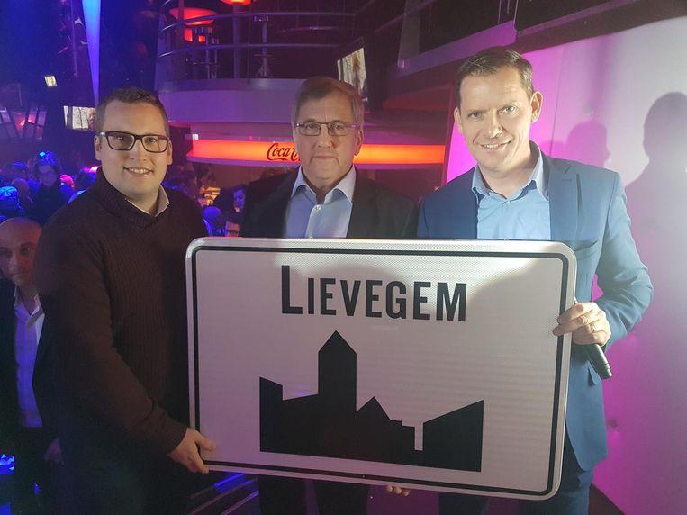 Waarnemend burgemeester Kim Martens van Waarschoot, burgemeester Chris de Wispelaere van Lovendegem en burgemeester Tony Vermeire van Zomergem tonen het bord 'Lievegem' aan een overvolle Kokorico.
