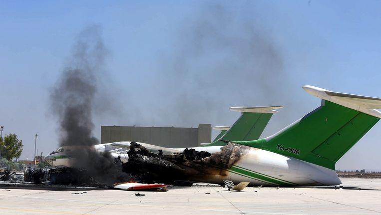Rook stijgt op uit een verwoest vliegtuig op het vliegveld van Tripoli. Beeld epa