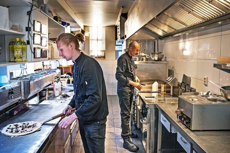 Ondernemer Rens Bekkers (links) bereidt een pizza in een van zijn zes digitale restaurants in de Amsterdamse Jordaan. Beeld Guus Dubbelman / de Volkskrant