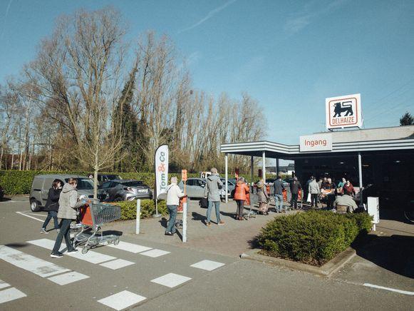 Aanschuiven aan de Delhaize, nu het aantal klanten in de winkel beperkt wordt.