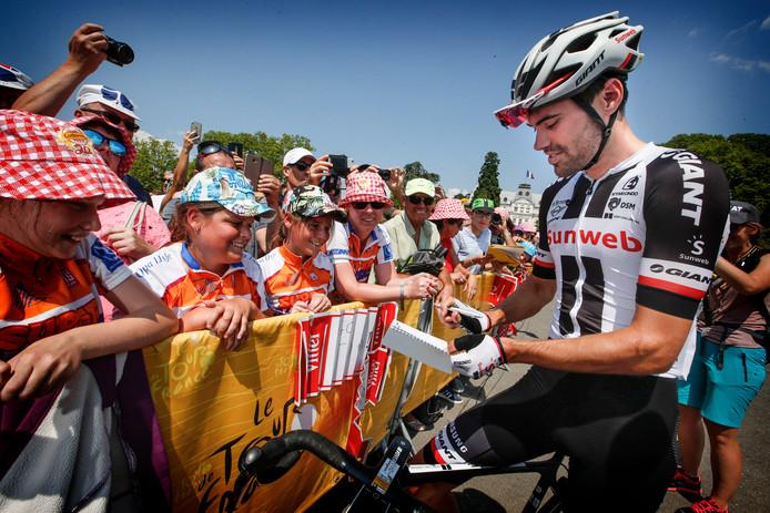 Tom Dumoulin deelt handtekeningen uit aan Nederlandse wielerfans voor de tiende etappe.