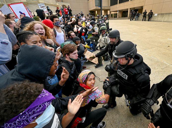 Les policiers mettent un genou à terre devant les manifestants rassemblés devant la Spokane County Courthouse à Spoken dans l'Etat de Washington, dimanche.