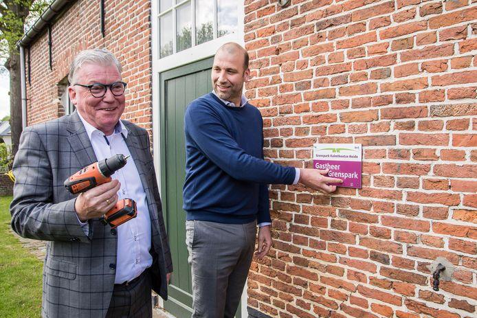 Martin Groffen, voorzitter van het Grenspark Kalmthoutse Heide, bevestigt het eerste nieuwe bordje van Gastheer van het Grenspark bij de Kiekenhoeve in Essen.