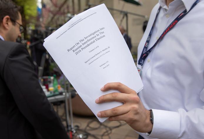 Een journalist houdt een geredigeerde versie van het rapport van Mueller vast