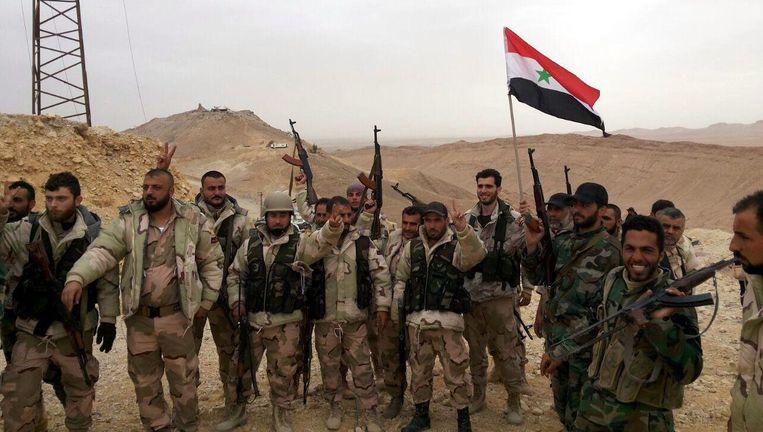 Syrische soldaten zwaaien met de Syrische vlag in Palmyra. Beeld epa
