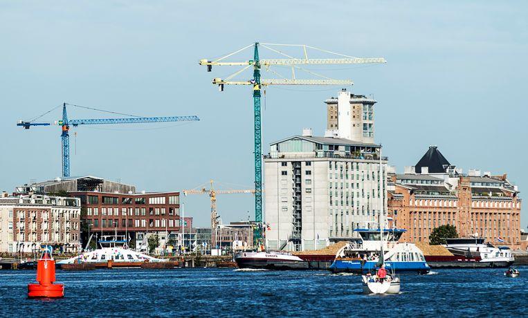 De woningmarkt in Amsterdam, Rotterdam, Den Haag en Utrecht is 'zeer gespannen', waardoor extra woningen bouwen noodzakelijk is. Hierboven zijn werkzaamheden te zien bij het Amsterdamse IJ.  Beeld ANP