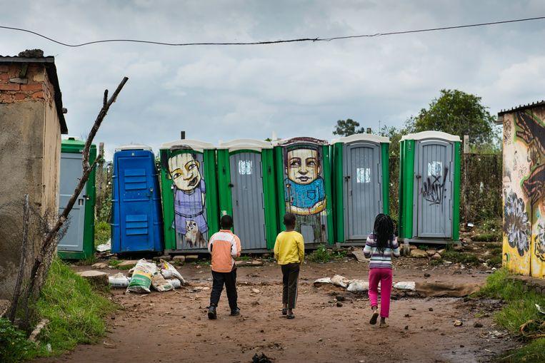 Groene dixietoiletten in de straten van sloppenwijk Freedom Charter in het Zuid-Afrikaanse township Soweto. Beeld Bram Lammers