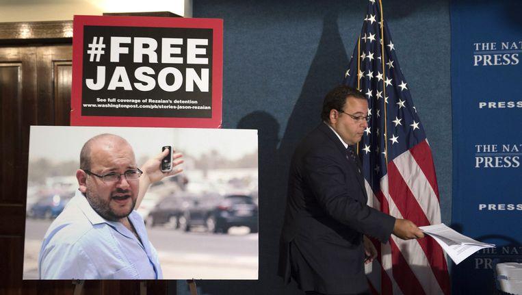 Een foto van Jason Rezaian in the National Press Club in Washington D.C. Zijn broer, Ali Rezaian, loopt ernaast. Beeld AP