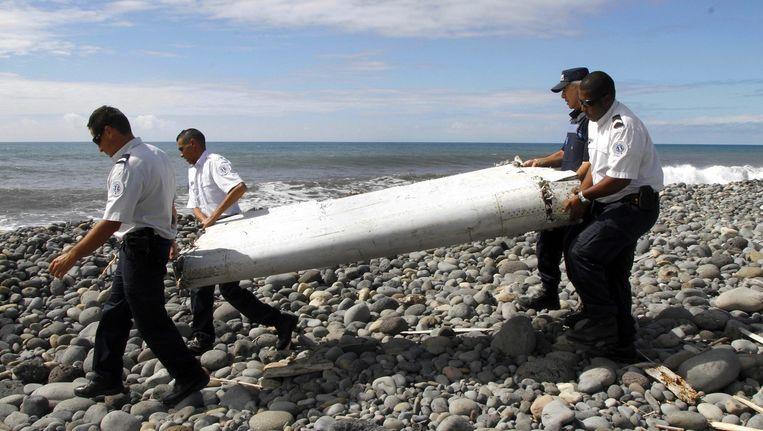 Agenten met het gevonden wrakstuk op Reunion. Beeld epa