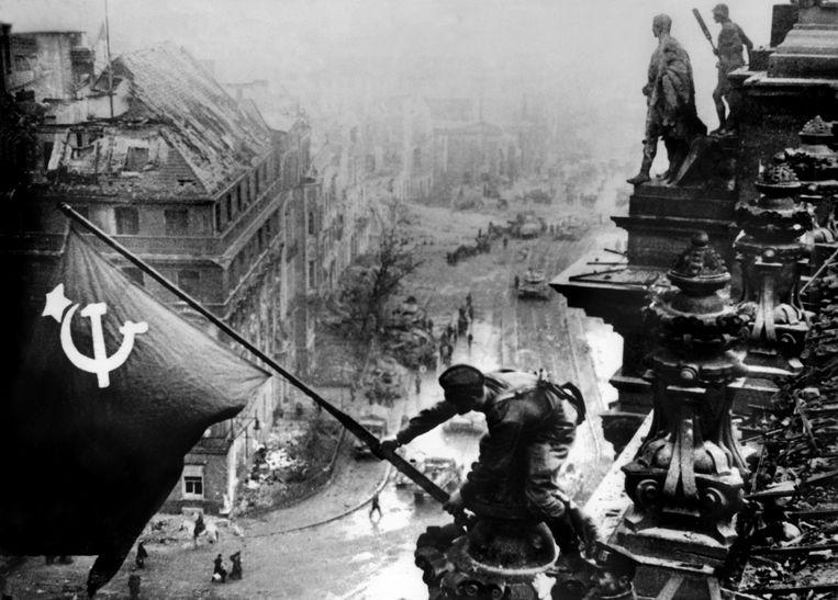 Een soldaat van het Rode Leger plant in 1945 de vlag van de Sovjetunie op het dak van de Duitse Rijksdag. Beeld ANP