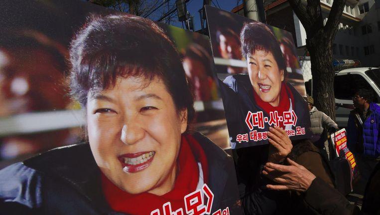Aanhangers van Park Geun-hye houden foto's van de president vast. Beeld afp