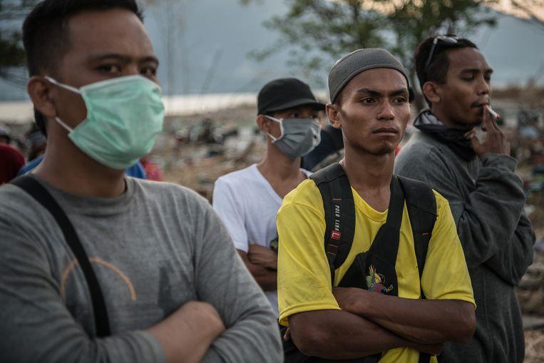 Mannen wachten af tijdens een zoektocht in een wijk van Palu.  Beeld null