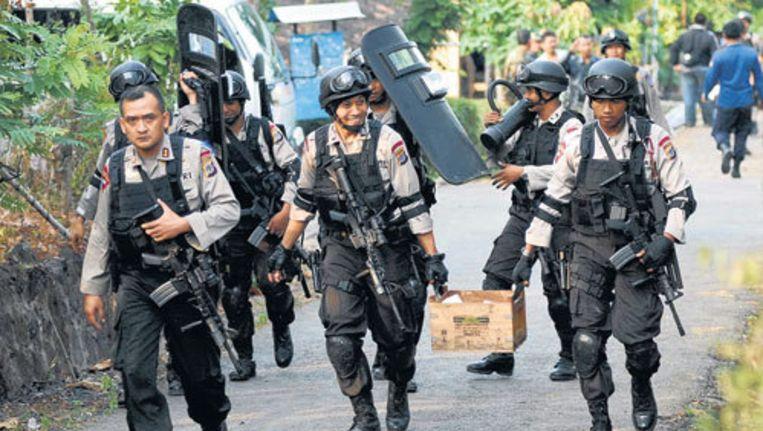 Agenten na de inval in de woning in Solo waar Mohammed Noordin Top zich bevond. Ze troffen er ook dozen munitie aan. Foto AP Beeld