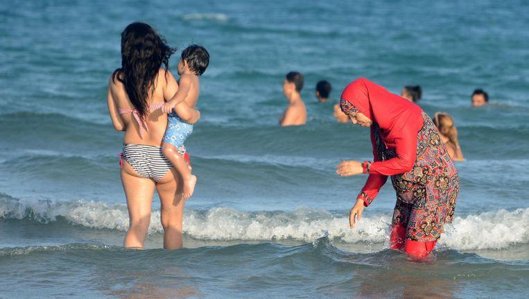 Een vrouwelijke badgast draagt een boerkini op het strand van de Tunesische plaats Ghar al Mehl. Beeld afp