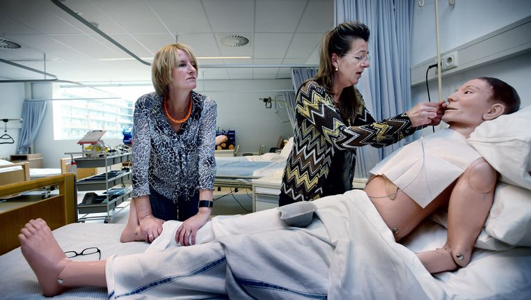 ROC-docent Barbera Lampe kijkt toe hoe laatstejaarsstudente Petra Klinkert oefent op een pop om een sonde in te brengen. Beeld Jean-Pierre Jans (www.jeanpierrejans.nl)