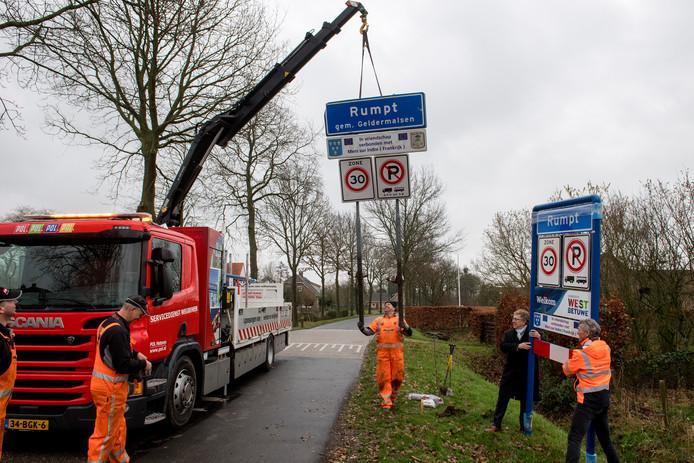 Een van de oude plaatsnaamborden bij Rumpt werd eerder deze week vervangen. Burgemeester Harry Keereweer (tweede van rechts) hield een oogje in het zeil.