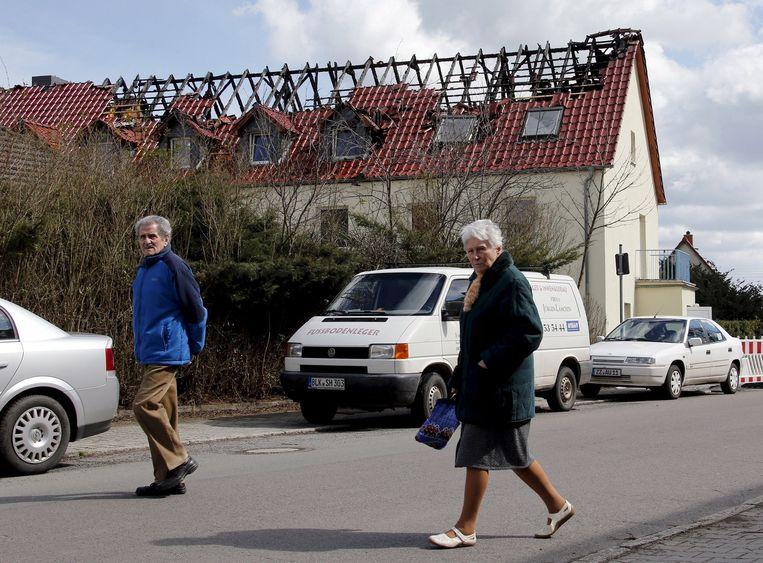 Inwoners van Tröglitz lopen langs een gebouw waarin asielzoekers opgevangen zouden worden. Het is door brand verwoest. Beeld reuters